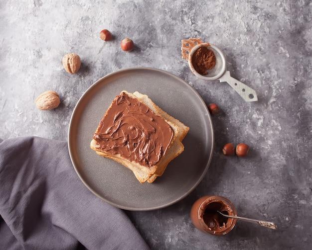 Brottoast mit schokoladencremebutter, glas schokoladencreme