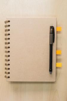Brown-anmerkungsbuch mit schwarzem stift auf holz