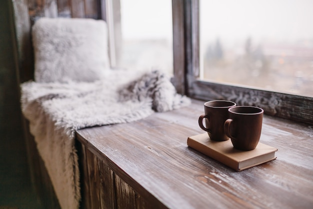 Brown cups stehen auf einem buch auf holzfensterbank