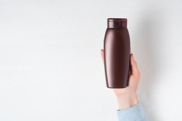 Brown-flasche für kosmetik in einer weiblichen hand.