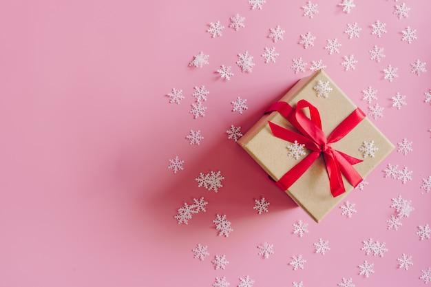 Brown-geschenkbox auf dem rosa hintergrund mit weihnachtsdekoration.