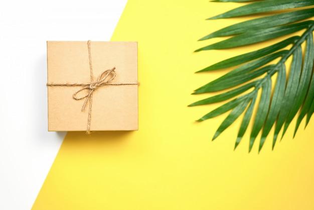 Brown-geschenkbox mit fliege und grasblume platzierte die seite, um schön auszusehen.