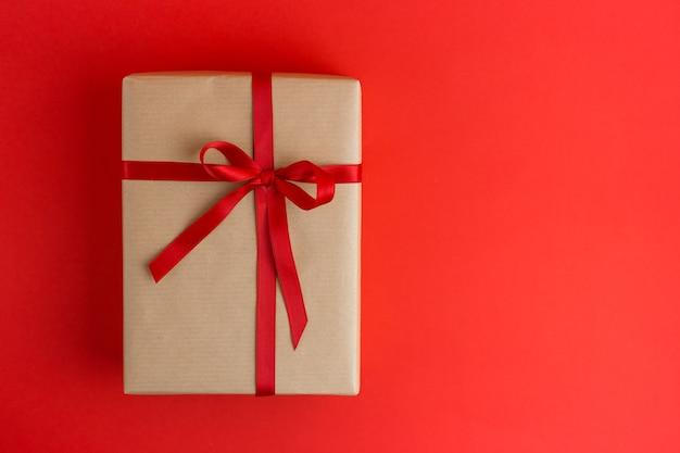 Brown-geschenkbox mit roten bändern auf rotem hintergrund. flacher lay-stil. geschenk für weihnachten, urlaub oder einen geburtstag.
