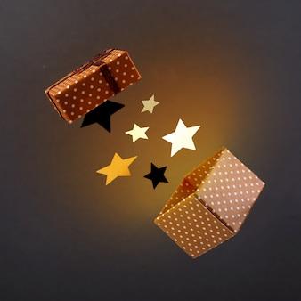 Brown-geschenkbox mit sternen und gelbem licht auf einer antigravitation der dunklen oberfläche.