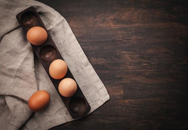 Brown-hühnereien im hölzernen ei stehen über dem rustikalen