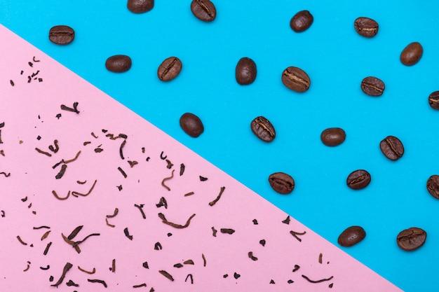 Brown-kaffeebohnen auf blauem hintergrund und trockenem tee auf rosa hintergrund. tee oder kaffee-konzept.