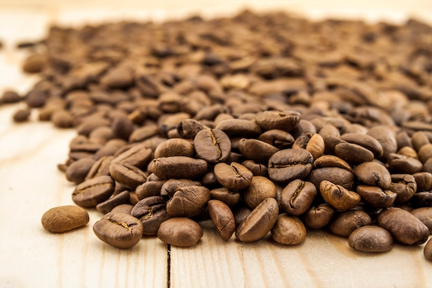 Brown-kaffeebohnen auf gelbem strukturiertem hintergrundabschluß des hölzernen brettes oben.