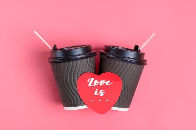 Brown-kaffeetassen, roter herz-förmiger aufkleber auf rosa hintergrund. alles gute zum valentinstag flach legen