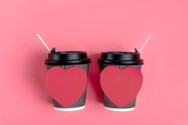 Brown-kaffeetassen, roter herz-förmiger aufkleber auf rosa hintergrund. liebe ist. konzept für kaffeeliebhaber, liebe ist. alles gute zum valentinstag flach legen
