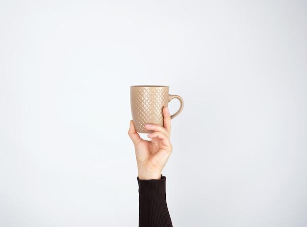 Brown-keramikschale in der weiblichen hand auf weiß