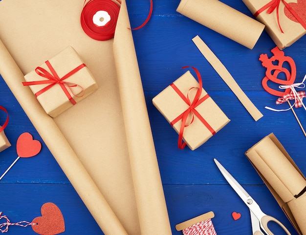 Brown-kraftpapier, verpackte geschenkbeutel und gebunden mit einem roten band, rotes herz, satz einzelteile für das machen von geschenken