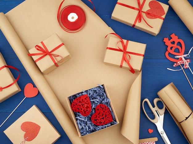 Brown kraftpapier, verpackte geschenktüten und mit einem roten band, rotes herz, set von gegenständen gebunden