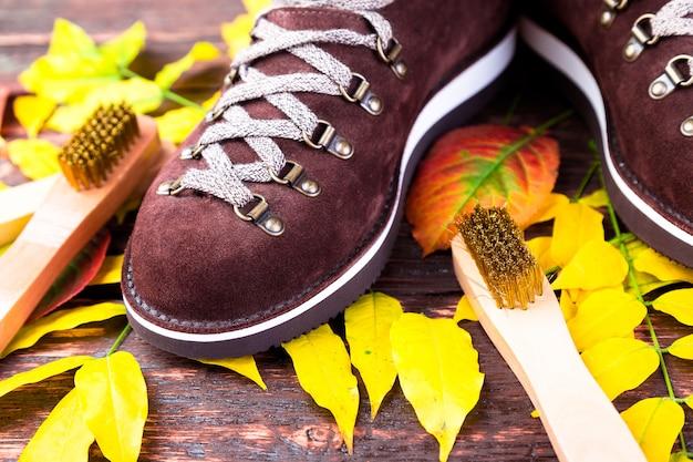 Brown-mannvelourslederstiefel auf hölzernem mit blättern. wildlederbürsten für schuhe. herbst- oder winterschuhe.