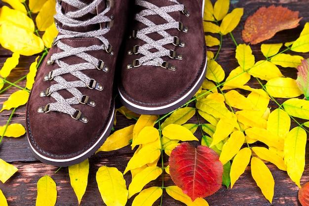 Brown-mannvelourslederstiefel auf holzoberfläche mit blätter herbst- oder winterschuhen