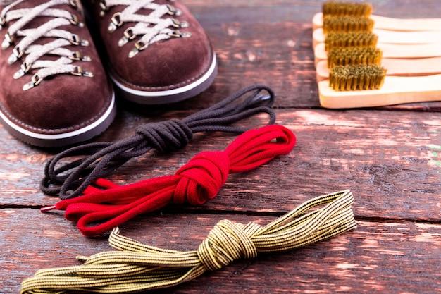 Brown-mannvelourslederstiefel mit bürstenschnürsenkeln auf hölzernem. herbst- oder winterschuhe.
