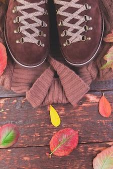 Brown-mannvelourslederstiefel mit strickjacke auf hölzernem mit blättern. herbst- oder winterschuhe. outfit.