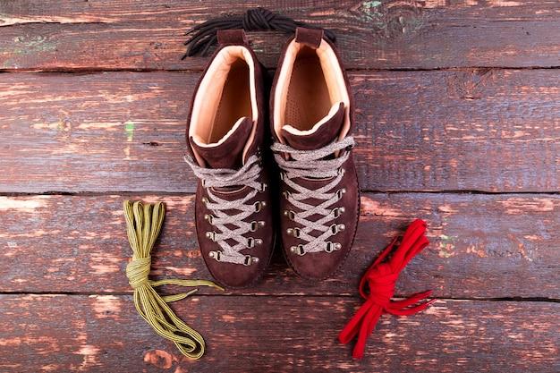 Brown-mannvelourslederstiefel und -spitzee auf hölzernem hintergrund. flach liegen. herbst- oder winterschuhe.