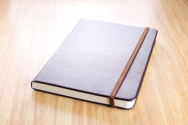 Brown-notizbuch der festen abdeckung mit elastischem bügel auf holztisch in der perspektivenansicht