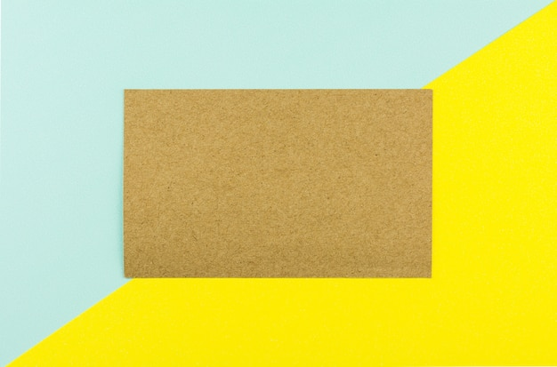 Brown-papier auf blauem und gelbem papierhintergrund.