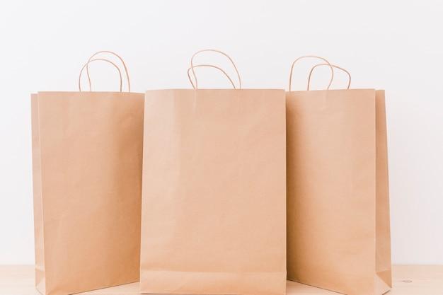 Brown-papiereinkaufstaschen auf hölzernem schreibtisch