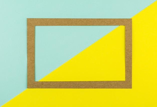 Brown-papierrahmen auf blauem und gelbem papierhintergrund. - platz für ihren text