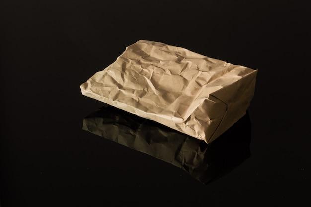 Brown-papiertüte lokalisiert auf reflektierendem schwarzem hintergrund