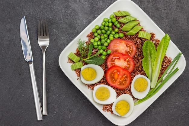 Brown reis eier und gemüse in weißen teller gabel und messer auf dem tisch