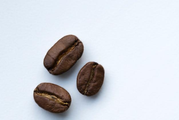 Brown-röstkaffeebohnen liegen auf einem weißen hintergrund.