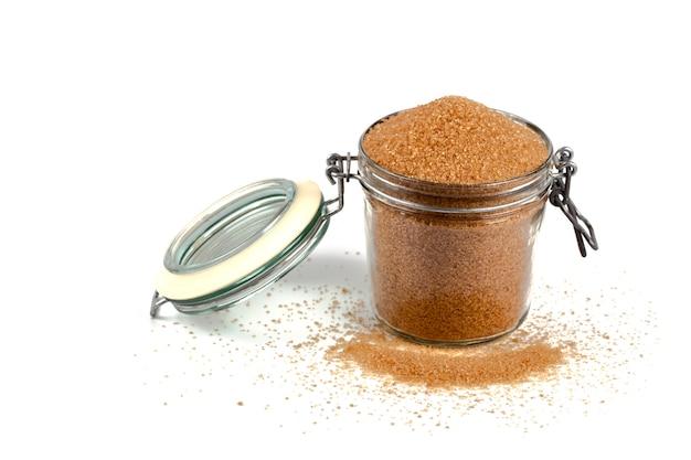 Brown-rohrzucker im glasgefäß lokalisiert auf weißem hintergrund.
