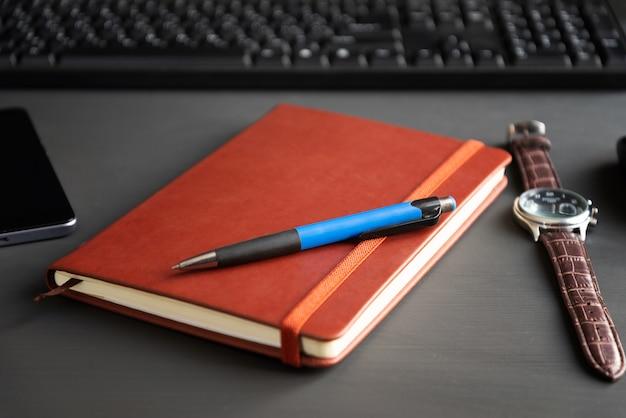 Brown-rotes notizbuch auf einem dunklen hintergrund.