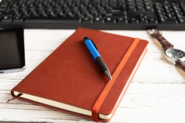 Brown-rotes notizbuch auf einem hellen hintergrund.