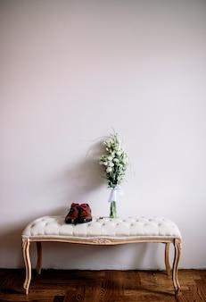 Brown-schuhe und hochzeitsblumenstrauß stehen auf einem sofa