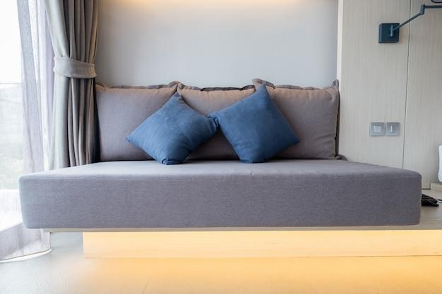Brown-sofa mit blauen kissen im schlafzimmer