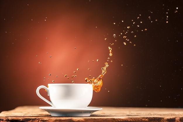 Brown spritzt getränk von der tasse tee auf einer braunen wand heraus