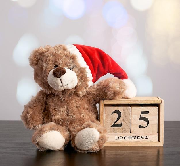 Brown-teddybär im roten hut, hölzerner kalender des schreibtisches mit dem datum am 25. dezember