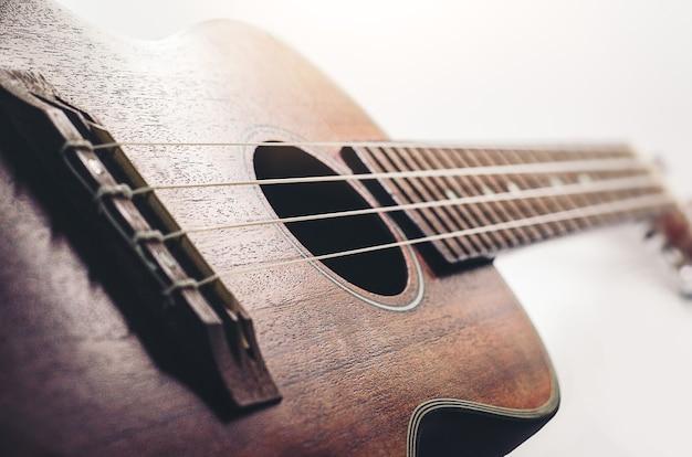 Brown-ukulelegitarre auf weißem hintergrundfeiertag entspannen sich pausezeit mit musik