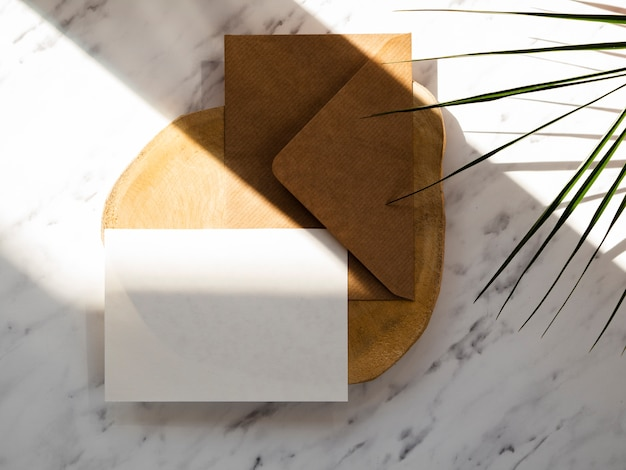 Brown-umschlag mit einem weißen freien raum auf einer hölzernen platte auf einem marmorhintergrund mit grünen blättern