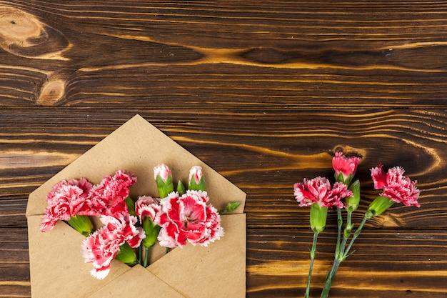 Brown-umschlag und rote gartennelkenblumen auf holztisch
