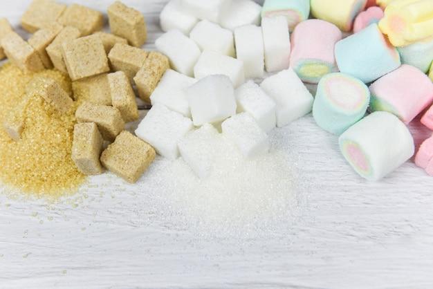 Brown-zucker, raffinierter zucker, zuckerwürfel und bunter süßigkeitsbonbon auf tabelle