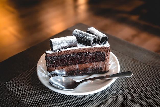 Brownie-kuchen mit schokoladenrolle auf die oberseite, die auf weiße keramikplatte gesetzt wird, haben teelöffel.