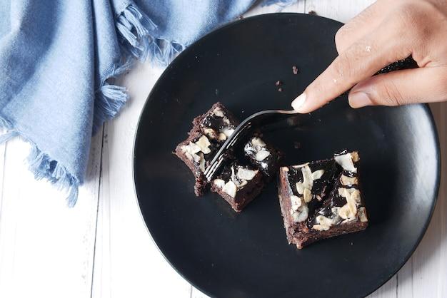 Brownie-scheibe mit gabel auf teller auf dem tisch schneiden