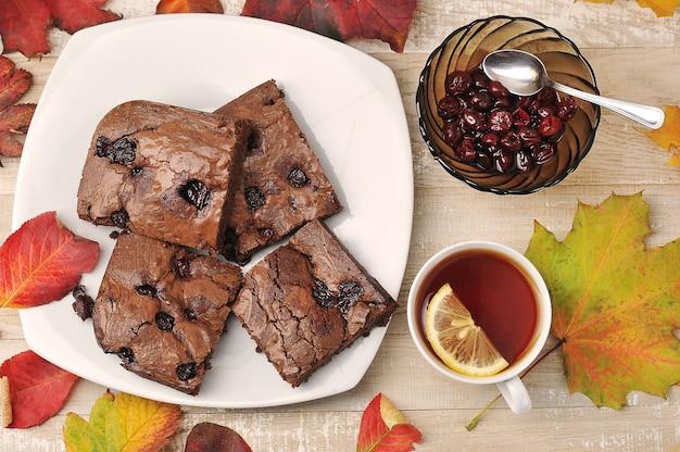 Brownie stücke mit kirschen und teetasse auf einem hölzernen hintergrund mit herbstlaub - draufsicht