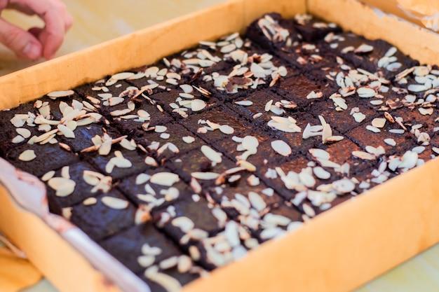 Brownies belegt mit mandeln in einem großen papierfach.
