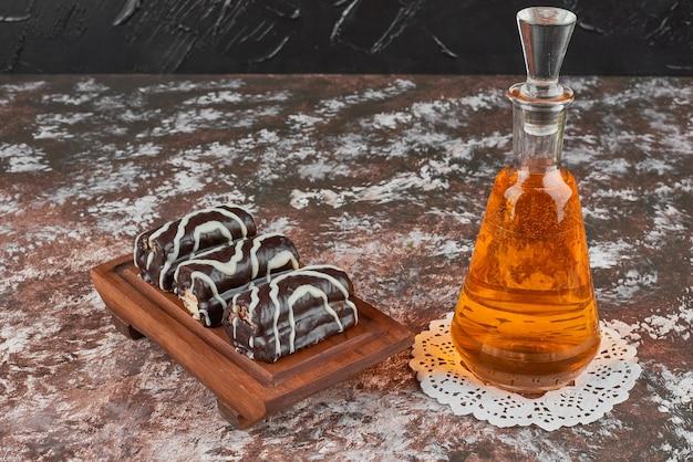 Brownies und eine flasche getränk auf einem holzbrett.