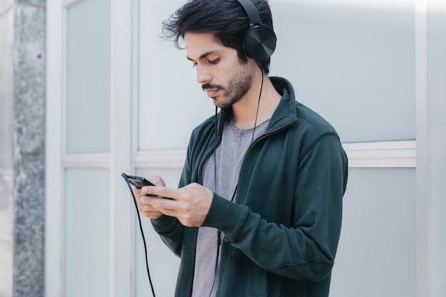 Browsing-telefon des jungen mannes mit kopfhörern