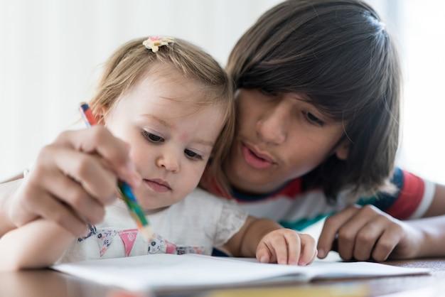 Bruder, der mit seiner kleinen schwester spielt und zeichnet