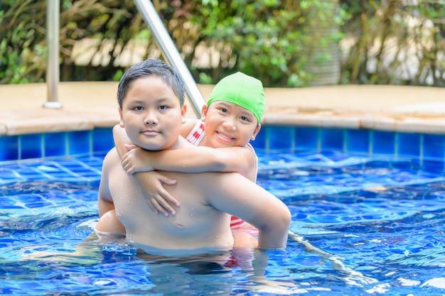 Bruder, der zurück schwester auf seinem im swimmingpool hält
