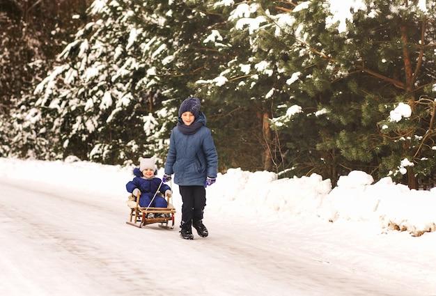 Bruder nimmt seine schwester im winter in der natur auf einen schlitten. kinderschlitten