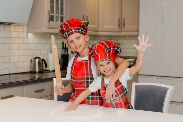 Bruder und schwester bereiten ein festliches abendessen in der küche des neuen jahres winterkonzept vor