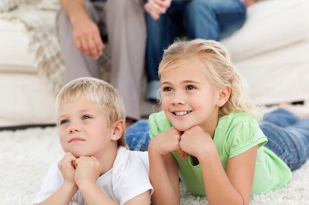Bruder und schwester, die mit ihren eltern auf dem boden fernsehen